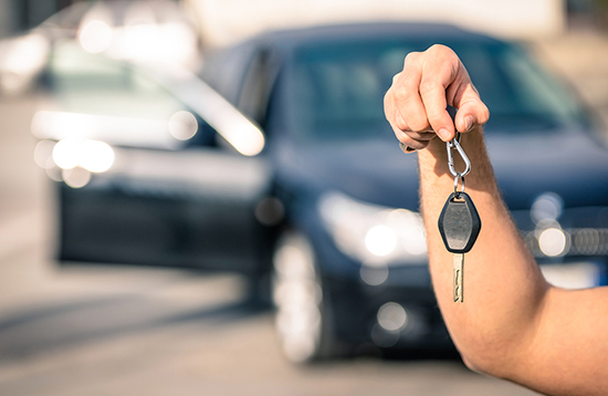 Man's hand holding modern car keys ready for rental - Concept of transportation with automobile second hand sale and trade
